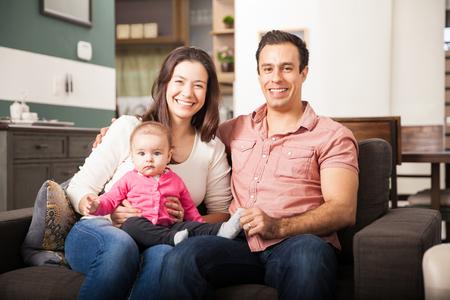 Portret van goed uitziende jonge ouders en hun baby meisje ontspannen thuis en glimlachend