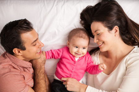 mom dad: feliz pareja hermosa y su bebé que se relajan en una cama juntos