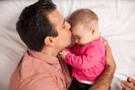forehead: Attractive young loving dad lying on a bed with his daughter and kissing her in the forehead