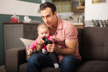 babysitting: Young attractive dad playing video games at home while taking care of her baby girl