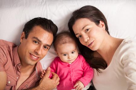 Portret van boven van een mooie jonge Latijns-familie met een baby meisje ontspannen in een bed thuis