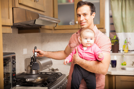 single father: Portrait of a young Hispanic single father holding his baby girl while cooking breakfast at home
