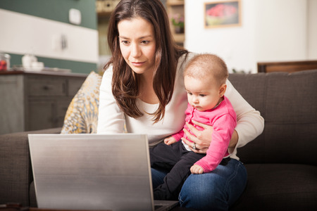 Pretty young single mom working at home on a laptop computer while holding her baby girl