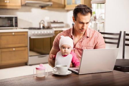 Attractive young single dad working on a laptop computer at home while taking care of his baby daughter Stockfoto
