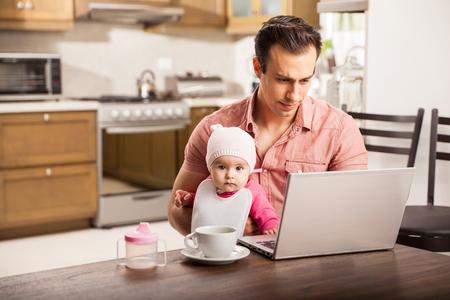 Atrakcyjna młoda single tata pracuje na komputerze w domu, dbając o jego córeczki