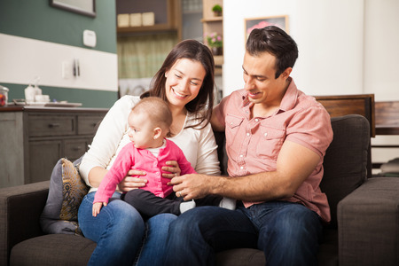 New Hispanic parents spending time with their baby girl in the living room