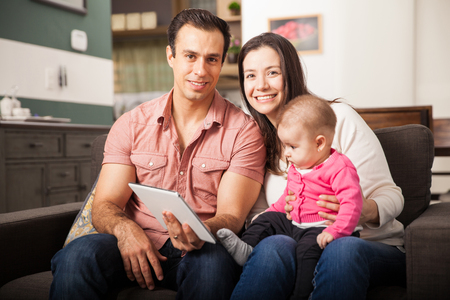 using tablet: Portrait of a beautiful Hispanic couple using a tablet computer with their baby daughter at home Stock Photo