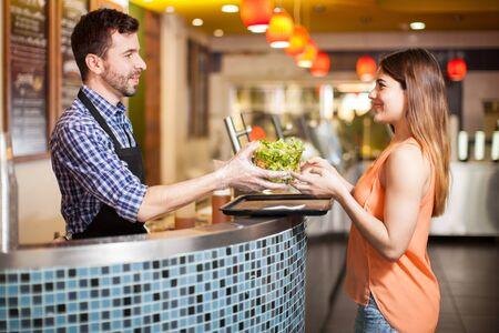 Vista de perfil de un hombre joven que trabaja en un bar de ensaladas y dar algo de comida sana a un cliente Foto de archivo