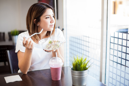 eating salad: Good looking young brunette enjoying a salad and a smoothie while looking out the window in a restaurant