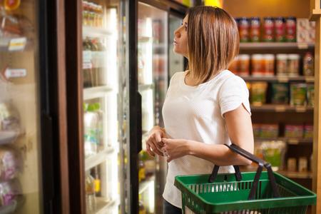 Mooi jong brunette die wat doen die bij een supermarkt winkelen en een ijskast bekijken