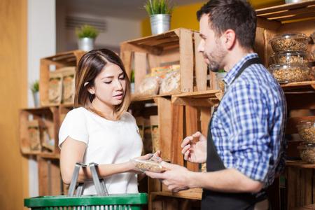 귀여운 갈색 머리가 지역 식료품 가게에서 점원의 도움을 받고있다.