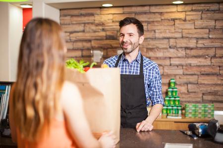 pagando: Apuesto cajero varón joven que ayuda a un cliente a la caja registradora y sonriente Foto de archivo