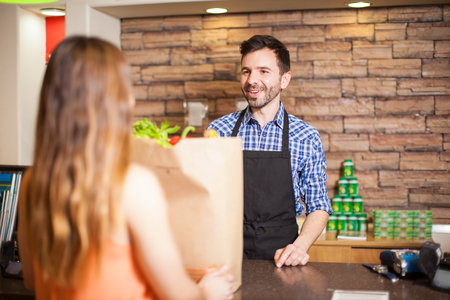 paying: Handsome young male cashier helping a customer at a checkout counter and smiling Stock Photo