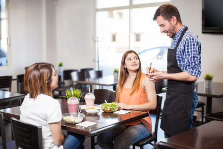 'young things': Young attractive waiter checking how things are going with some of his customers at a restaurant Stock Photo