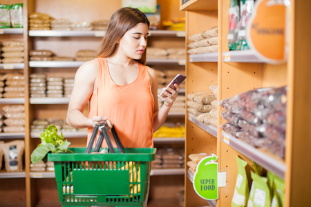 basket: Pretty young brunette carrying a basket full of groceries and using a smartphone in a supermarket
