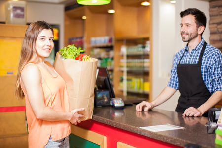checkout: Cute young brunette ready to pay for her groceries at a checkout counter in a store Stock Photo