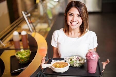 cafeteria tray: High angle view of a young woman carrying a tray with some food at a cafeteria and smiling Stock Photo