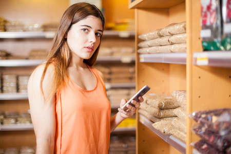 eye contact: Portrait of a gorgeous young woman using a smartphone in a grocery store and making eye contact