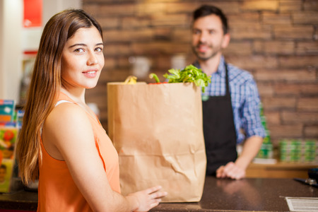 grocery store checkout: Portrait of a gorgeous young Hispanic woman buying some groceries at a supermarket