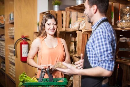 store clerk: Portrait of a cute happy Hispanic customer getting some help from a store clerk at a grocery store