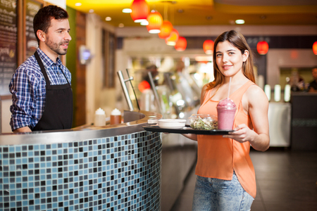 cafeteria tray: Pretty young brunette holding a tray with some healthy food in a cafeteria Stock Photo