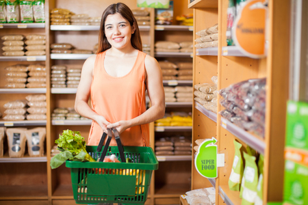 Good looking young woman buying some organic food at a grocery store and smiling