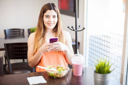 Portrait of a pretty young woman updating her social media status while eating some healthy food at a restaurant