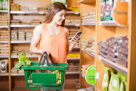 Happy girl using her smartphone to update her social media status while buying some groceries and healthy food at a store