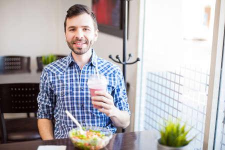 hombre comiendo: Retrato de un hombre latino joven comer algunos alimentos saludables y disfrutar de un batido solos en un restaurante