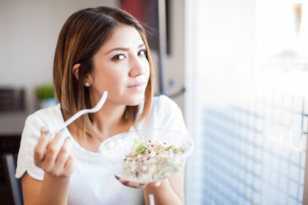 eye contact: Portrait of a beautiful young brunette eating a salad at a restaurant and making eye contact Stock Photo