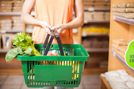 Closeup of a young woman holding a basket full of groceries and organic healthy food in a supermarket Stock Photo