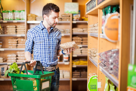 food market: Attractive man with a beard reading a product label while buying groceries at a store