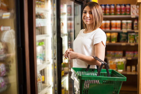 Portrait of a pretty Latin woman carrying a basket and buying groceries at a supermarket Stock Photo