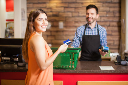 Portrait of a gorgeous young Hispanic brunette using a credit card to pay for her groceries at a store Stock Photo
