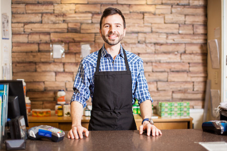 bel homme: Portrait d'un jeune propri�taire d'une entreprise hispanique beau debout au comptoir de la caisse et souriant Banque d'images