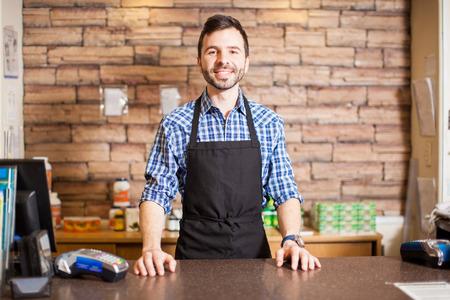 cash money: Retrato de un propietario de negocio apuesto joven hispano de pie en la caja y sonriendo