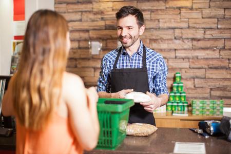 Cajero y la cara sonriente del cliente a cara, mientras que la compra de alimentos en un supermercado Foto de archivo