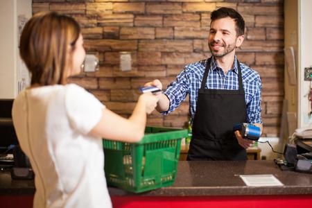 pagando: apuesto joven con una barba de tomar una tarjeta de crédito de un cliente en una tienda de comestibles