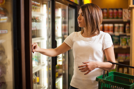 Pretty young woman carrying a basket and looking at some products in a refrigerator at the supermarket
