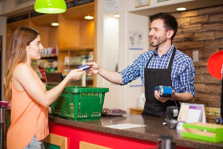 Vista de perfil de una mujer joven que paga con una tarjeta de crédito a un empleado de la tienda en un supermercado Foto de archivo