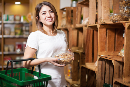 Beautiful young brunette buying some groceries and granola at a supermarket and smiling