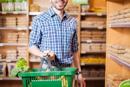 Closeup of a young man carrying a basket full of groceries while shopping in a store Stock Photo