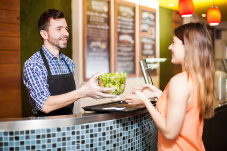 handing over: Young Hispanic man working at a restaurant and handing over a finished salad to a customer