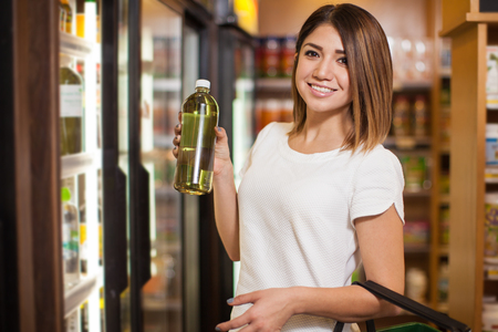 chlorophyll: Cute young woman buying some water with chlorophyll at a grocery store