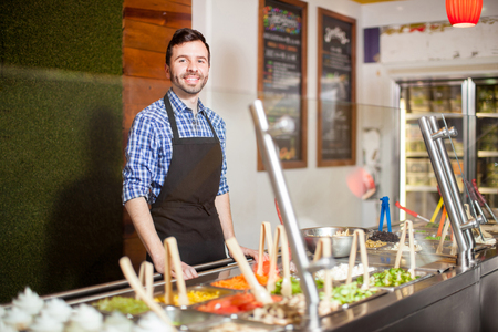 Portrait of a good looking Hispanic man working at a salad bar in a restaurant Foto de archivo