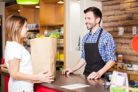 Vista de perfil de un cajero varón joven que ayuda a un cliente paga por todos sus comestibles en una tienda