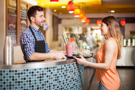 Vista de perfil de una mujer joven comprar una ensalada, una sopa y un batido en un restaurante