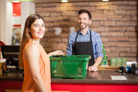 pagando: Retrato de una bella joven morena América pagando por su tienda de comestibles en la caja en una tienda