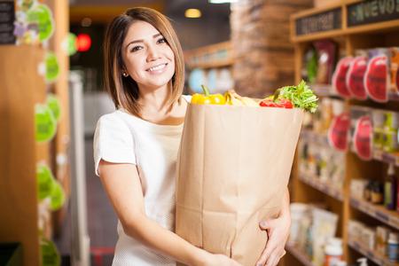 Gorgeous giovane donna che porta un sacchetto di acquisto, mentre l'acquisto dei generi alimentari in un negozio e sorridente
