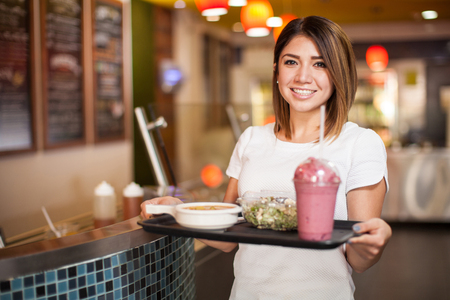veggie tray: Portrait of a beautiful Latin woman with a tray full of food at a cafeteria Stock Photo